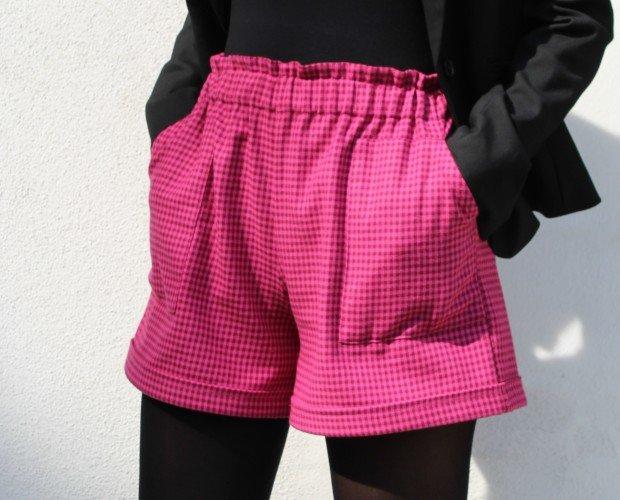 Pantaloncini a quadretti. Pantaloncini in tessuto a quadretti color fucsia, elastico in vita, tasche applicate.